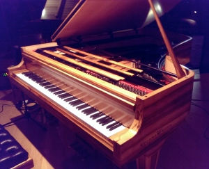 The Stuart & Sons studio grand piano. Note the extended range, fourth pedal and striking grain of the sassafras timber.